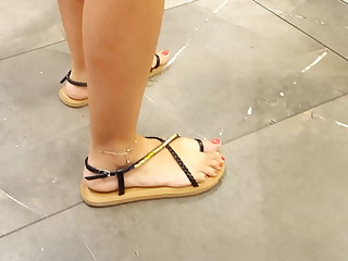 Her sexy long feets red toes at shoe shopping