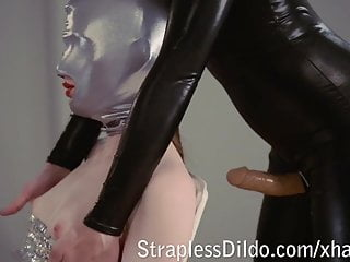 Domina in shiny catsuit gives strapon